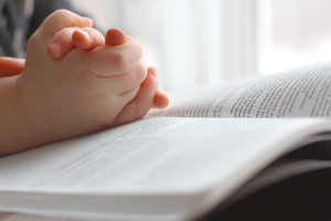 the hands of a young Christian child are folded in prayer over the book the Holy Bible